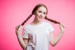 Ungt attraktivt flickainnehav för långa flätade trådar Stående av den härliga le kvinnan med den flätad tråden för skönhethår arkivbilder