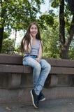 Ungt attraktivt flickasammanträde på bänk oklarheter över vita parksommartrees leende foto Arkivfoton