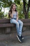 Ungt attraktivt flickasammanträde på bänk oklarheter över vita parksommartrees leende foto Fotografering för Bildbyråer