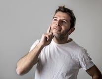 Ungt attraktivt göra en gest för man som är fundersamt som, om dagdrömma för Fotografering för Bildbyråer