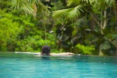 Ungt attraktivt koppla av för kvinna som är lyckligt på tropisk simning för strandlyxsemesterort på djungeloändlighetspölen som i arkivbilder