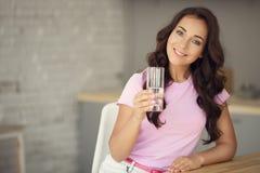 Ungt attraktivt kvinnadricksvatten på kök royaltyfri fotografi