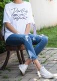 Ungt attraktivt kvinnligt modellsammanträde på trästol för tre ben royaltyfri foto