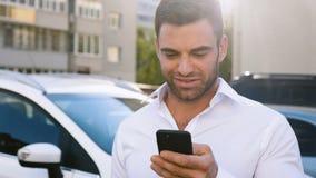 Ungt attraktivt mananseende på parkering nära kontorsbyggnad som skriver ett meddelande på hans smartphone stilig aff?rsman stock video