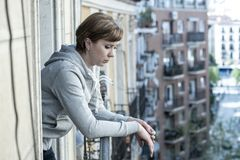 Ungt attraktivt olyckligt ensamt kvinnalidande från fördjupning på balkongen hemma Urban beskådar fotografering för bildbyråer