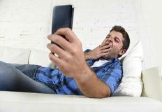 Ungt attraktivt trött och överansträngt falla gäspa sovande hemmastadd soffa med mobiltelefonen och den digitala minnestavlan royaltyfria foton