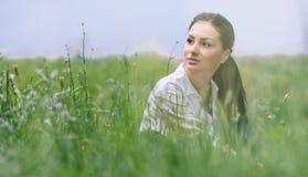 Ungt avslappnande kvinnasammanträde i gräset royaltyfri foto