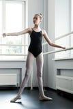 Ungt ballerinaanseende på balettbarren royaltyfri foto