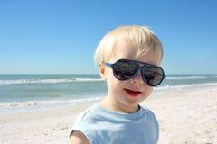 Ungt barn i solglasögon på stranden Arkivfoto