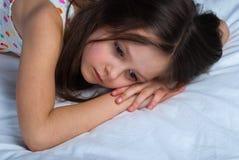 Ungt barn ligga som är vaket i hans säng Fotografering för Bildbyråer