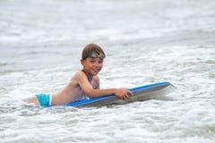Ungt barn med en bodyboard på stranden Royaltyfria Foton