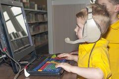 Ungt barn på en dator Arkivfoto
