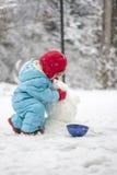 Ungt barn som bygger en snögubbe Royaltyfri Foto