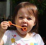 Ungt barn som har gyckel som blåser bubblor Arkivfoton