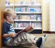 Ungt barn som läser en bok på arkivet royaltyfri fotografi