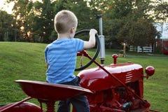 Ungt barn som låtsar för att köra den röda antika traktoren royaltyfri fotografi