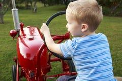 Ungt barn som låtsar för att köra en röd traktor arkivfoton