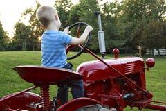 Ungt barn som låtsar för att köra en röd traktor fotografering för bildbyråer