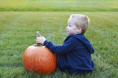 Ungt barn som rymmer hans stora pumpa för halloween i ett gräs- royaltyfria foton