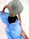 Ungt barn som slås in i en handduk på stranden arkivfoton