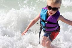 Ungt barn som spelar i havvågor i flytväst Royaltyfria Foton