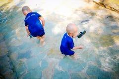 Ungt barn som spelar utanför i strömmen Royaltyfri Foto