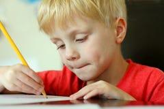 Ungt barnteckning på papper med blyertspennan Royaltyfri Bild