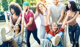 Ungt blandras- folk som har gyckel samman med shoppingvagnen - Millenial vänner som delar tid med spårvagnar på den kommersiella  royaltyfri fotografi