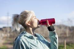 Ungt blont flickadricksvatten under att jogga för morgon arkivbilder