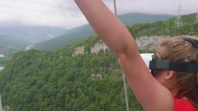 Ungt blont i virtuell verklighetexponeringsglas kastar hennes hand upp mot bakgrund av den gröna skogsbevuxna bergdalen arkivfilmer