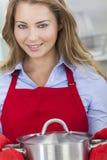 Ungt blont kök för kvinnaflickamatlagning Fotografering för Bildbyråer