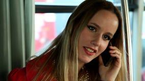 Ungt blont kvinnaanseende i spårvagn och samtal på telefonen arkivfilmer
