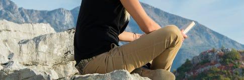 Ungt blont kvinnasammanträde på kanten av bergklippan som läser en bok mot härligt bergmaximum Sund livsstil fotografering för bildbyråer