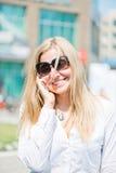 Ungt blont kvinnasamtal vid den utomhus- telefonen Arkivbilder