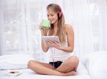 Ungt blont sammanträde på sängen som lyssnar till musik- och drinkte Arkivfoton
