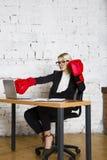 Ungt blont skönhetaffärskvinnasammanträde på en kontorstabell med bärbara datorn, anteckningsboken och exponeringsglas i dräkt oc Royaltyfri Foto