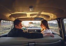 Ungt bröllopparsammanträde som ler inom den retro bilen och ser de precis kramar den gifta omfamningen den inre bilen Brud Royaltyfria Foton