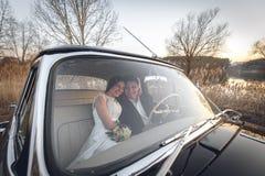 Ungt bröllopparsammanträde som ler inom den retro bilen och ser de precis kramar den gifta omfamningen den inre bilen Brud Royaltyfri Fotografi
