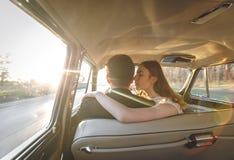 Ungt bröllopparsammanträde som ler inom den retro bilen precis kramar den gifta omfamningen den inre bilen brud som kramar brudgu Arkivfoton
