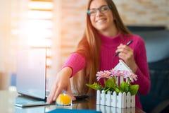 Ungt brunettarbete p? hennes kontorsskrivbord med dokument och b?rbara datorn Aff?rskvinna som arbetar p? skrivbordsarbete arkivbilder