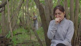 Ungt brunettkvinnanederlag bak ett träd från en man med en yxa arkivfilmer