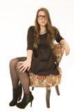 Ungt brunettkvinnasammanträde i en blom- stol som bär den svarta klänningen Arkivfoton