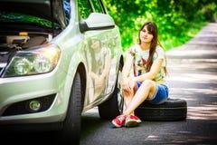 Ungt brunettkvinnasammanträde nära en silverbil på vägrenen med ett brutet hjul Arkivbilder