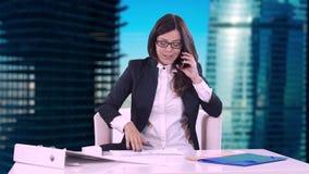 Ungt brunettsammanträde bak ett skrivbord i regeringsställning och tala på telefonen På tabellen är dokument och avtalet stock video