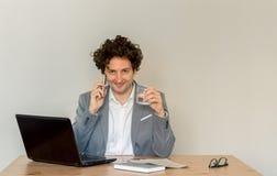 Ungt Caucasian affärsmansammanträde på hans skrivbord och använda hans mobiltelefon framme av det tomma klara väggbegreppet arkivfoto