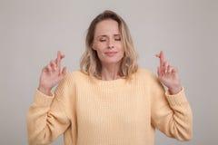 Ungt caucasian blont kvinnligt bokslut henne ?gon som korsar fingrar med hopp som f?rutser viktig nyheterna b?rande gul tr?ja fotografering för bildbyråer