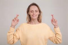 Ungt caucasian blont kvinnligt bokslut henne ?gon som korsar fingrar med hopp som f?rutser viktig nyheterna b?rande gul tr?ja royaltyfri foto