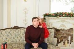 Ungt caucasian fadersammanträde med den lilla dottern på soffan nära dekorerade spisen Arkivbilder