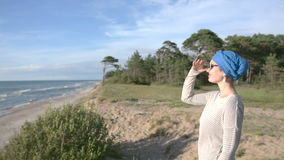 Ungt Caucasian kvinnaanseende på stranden i turbanen och solglasögon som ser till horisonten stock video