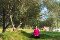 Ungt caucasian kvinnasammanträde under ett träd och meditera Arkivbild